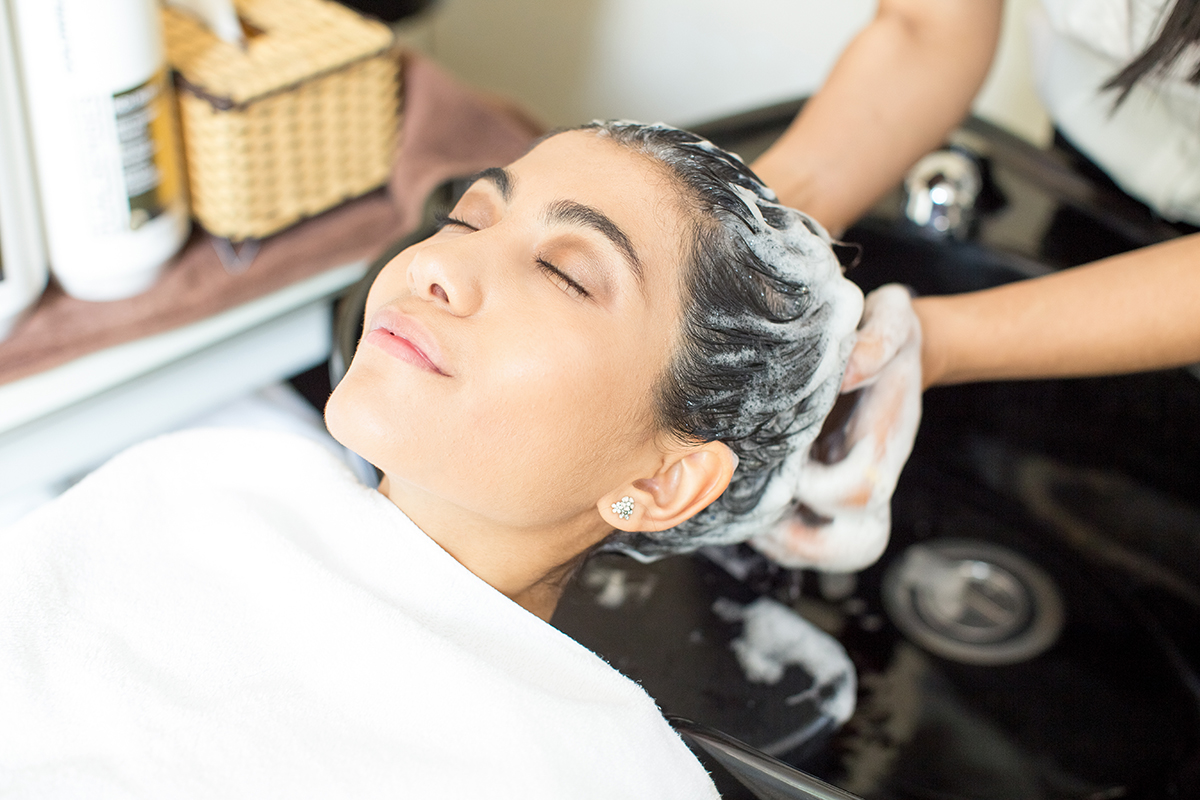Face of relaxed young Latin American woman enjoying hair washing in salon. Hairdresser washing hair of woman with shampoo